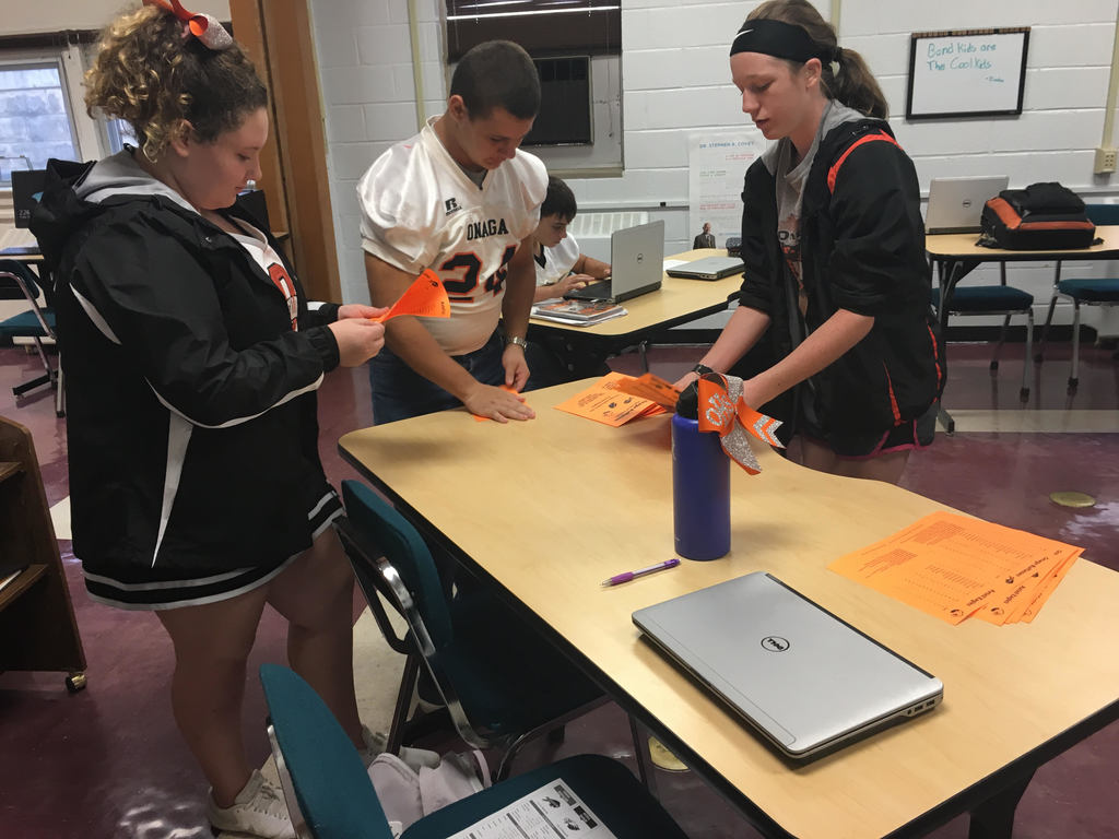 Onaga students folding sports programs.