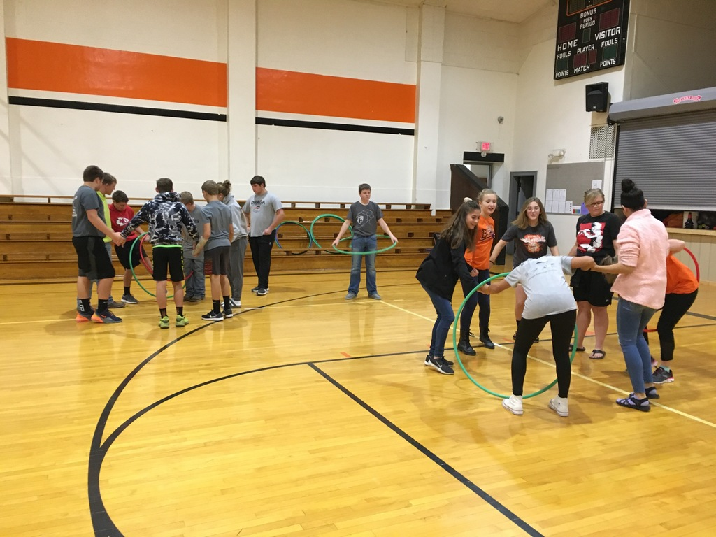 Students playing a game with hula hoops.